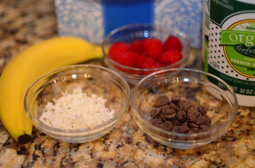 Banana, raspberries, chocolate chips, and granola for a yogurt parfait