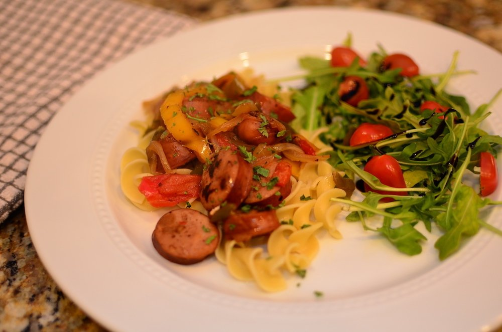 Chicken sausage and peppers over egg noodles with a side salad