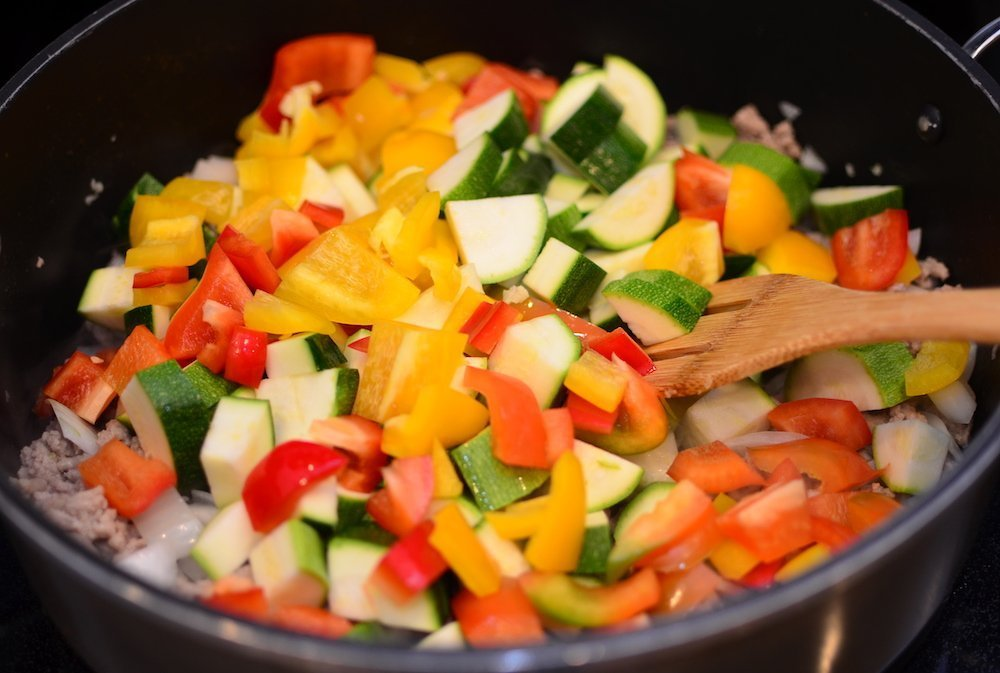 Zucchini, and bell peppers are added to ground turkey, onion and garlic in a large skillet