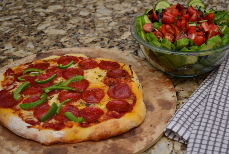 Pepperoni and green pepper pizza with a side salad