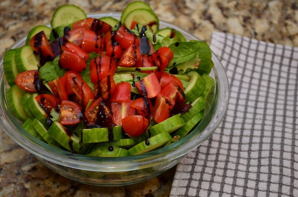 Prepared salad with spring mix, cucumbers, tomatoes, and Trader Joe's Glaze dressing