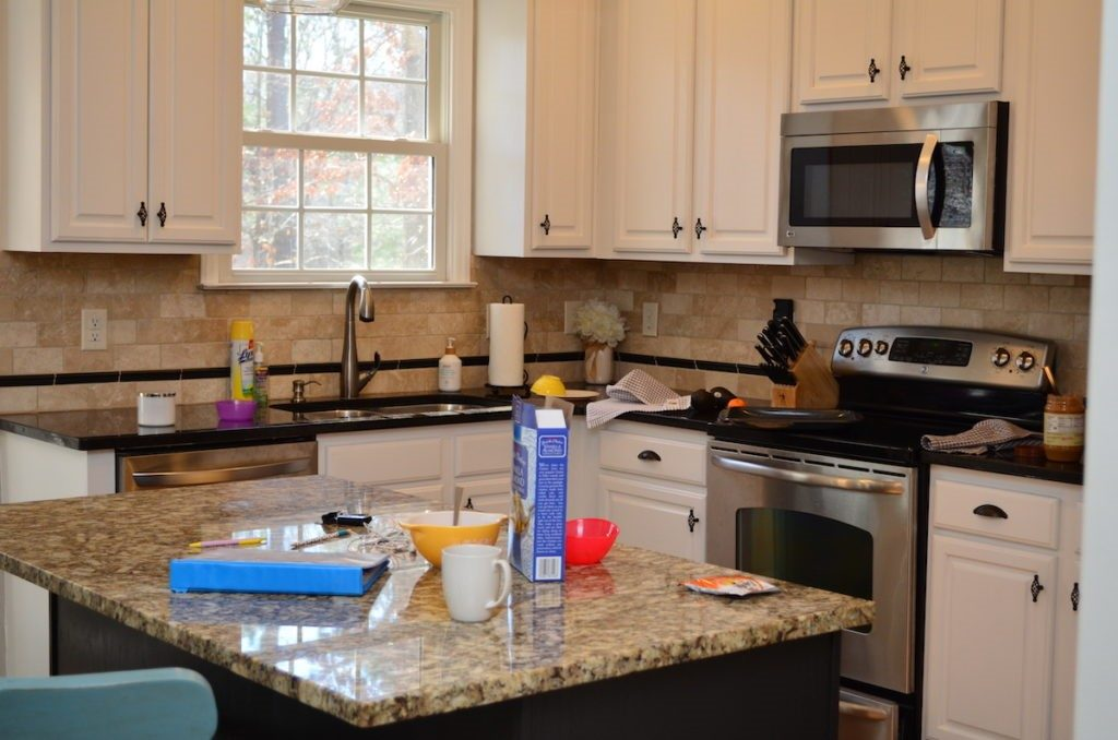 Cluttered kitchen countertops covered in dirty dishes, cereal boxes and keys