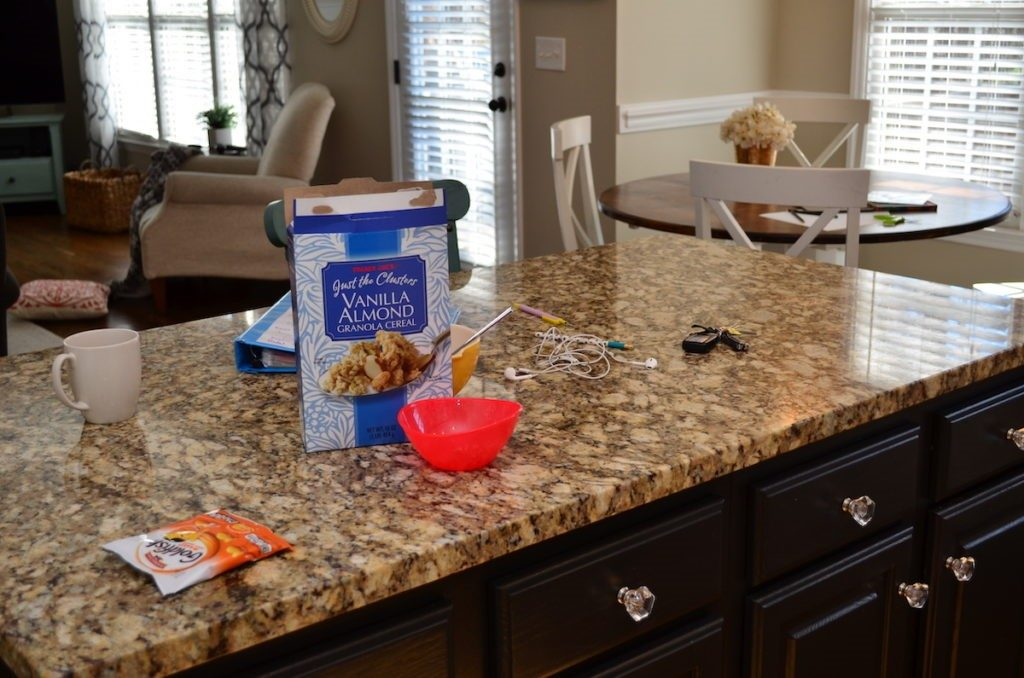 Kitchen counter covered in dirty dishes, keys, wrappers, and cereal boxes.