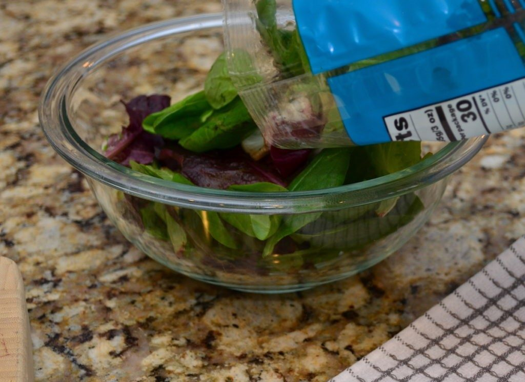 Pouring spring mix greens into a glass bowl.