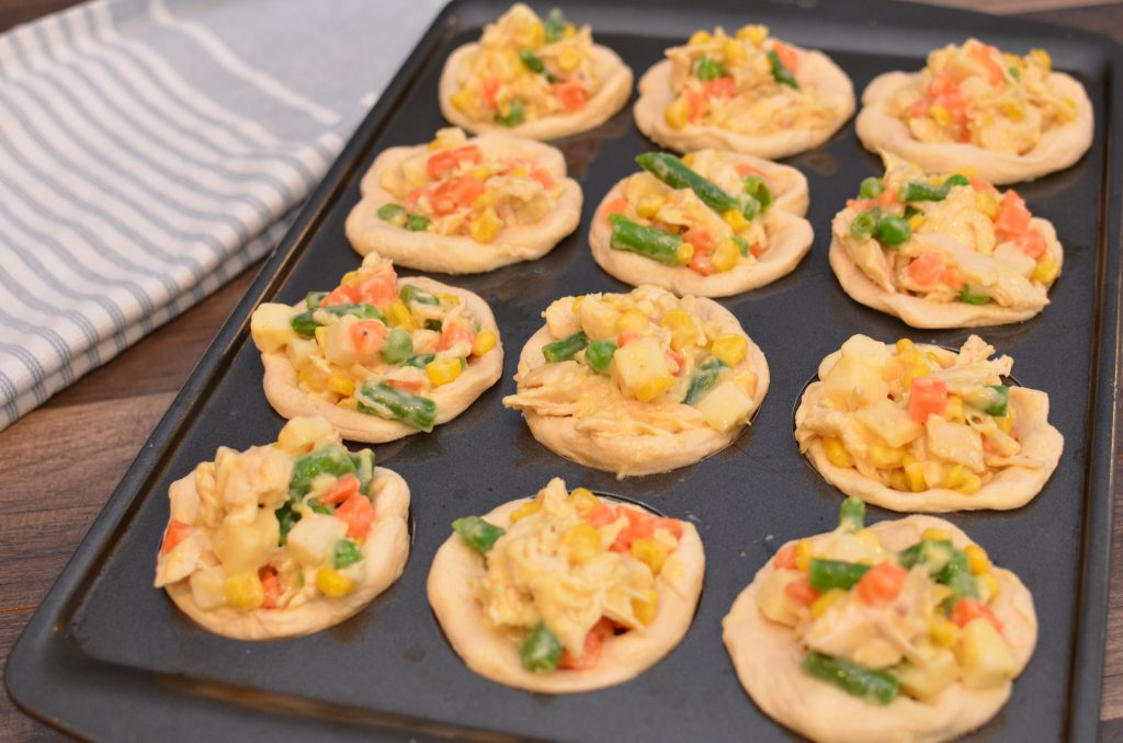 Chicken and vegetables placed in biscuit lined muffin tins