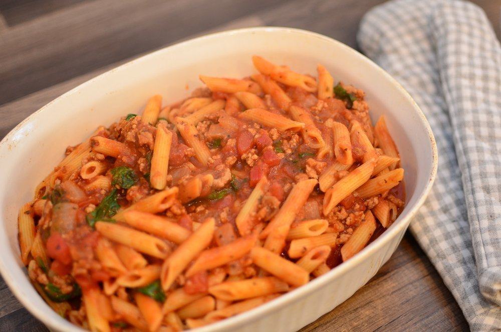 Pasta and sauce in a baking dish forBaked spinach and turkey Italian pasta